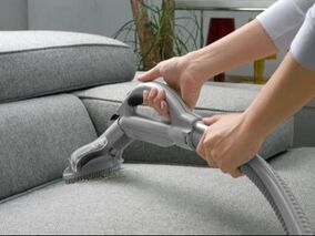 person vacuuming upholstery